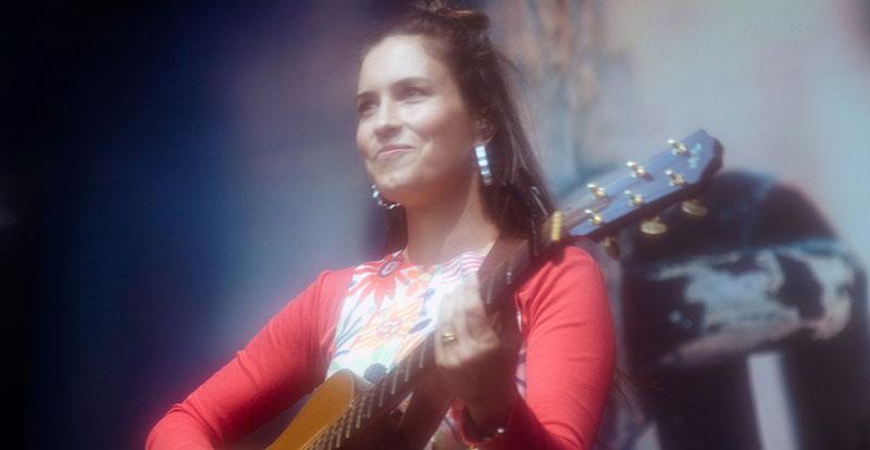 Missy Higgins on stage smiling strumming guitar