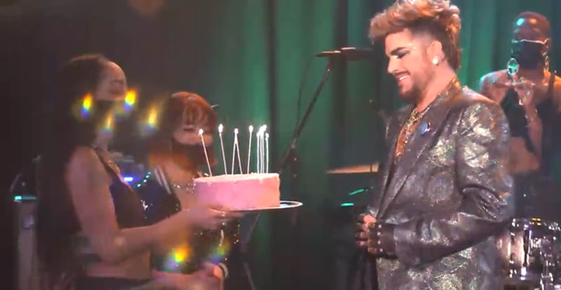 Two women presenting Adam Lambert with a cake lit with candles