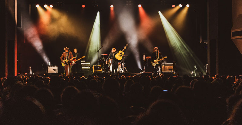 Long shot of five musicians on stage with coloured lights beaming over the crowd