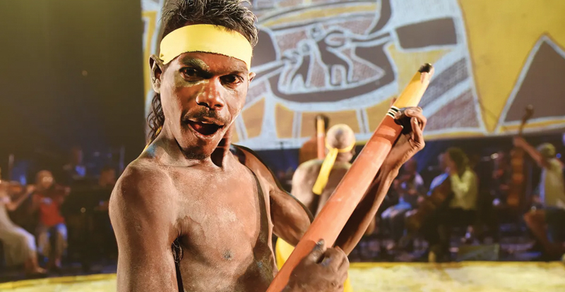 Young Aboriginal Australian man performing in traditional costume
